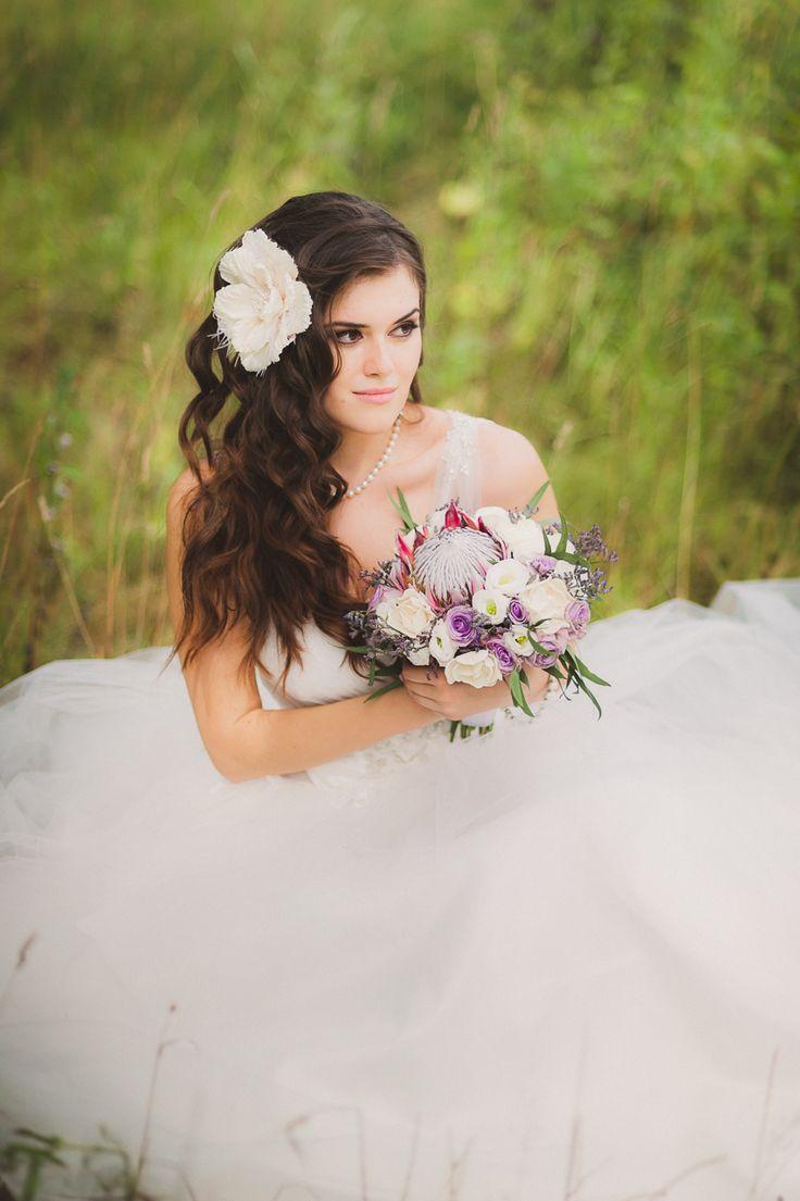 Фиолетовая свадьба. Невеста с длинными волосами брюнетка, сидит на траве. Фиолетовый букет невесты и фиолетовыми розами. Белый цветок заколка в волосах