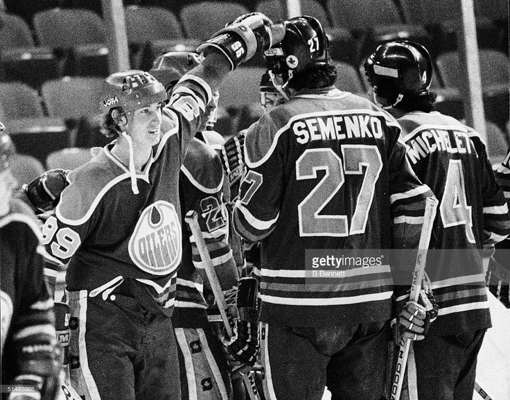 Canadian hockey players Wayne Gretzky, #99 for the Edmonton Oilers, and Dave Semenko (#27) celebrate a win with American teammate Joe Micheletti (#4) after a World Hockey Association (WHA) game against the New England Whalers, Springfield, Massachusetts, 1979.