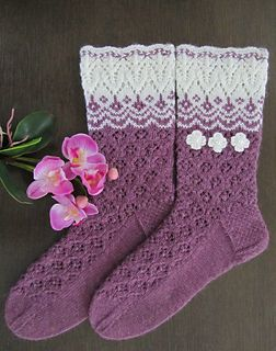 """These socks were designed as as """"sisters"""" to my leaf-patterned Helmike-socks. Knitted on double pointed needles, I combined lovely lace cuff with some stranded pattern and lace with small flowers. Any other color instead of violet or orange would look great and shiny with white. Or maybe instead of white some other color? :)"""