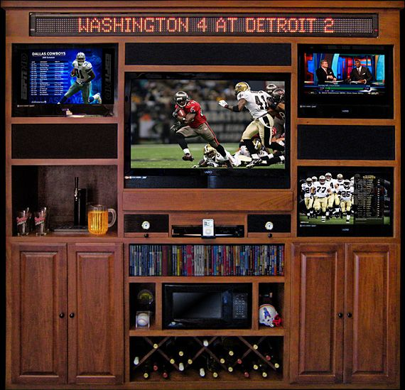 "The Man Wall. This all-in-one chunk of awesomeness features room for four TVs — one 52"" and two 26"" units are included — a 1200-watt Panasonic home theater with integrated speakers and wireless surround units, two 25-cigar humidors with gauges, a 32-bottle wine rack, a microwave, a live 7-foot sports ticker at the top with built-in computer, a full-size kegerator with tap, an iPod docking station, DVD player, and the ability to control it all via a single remote control."