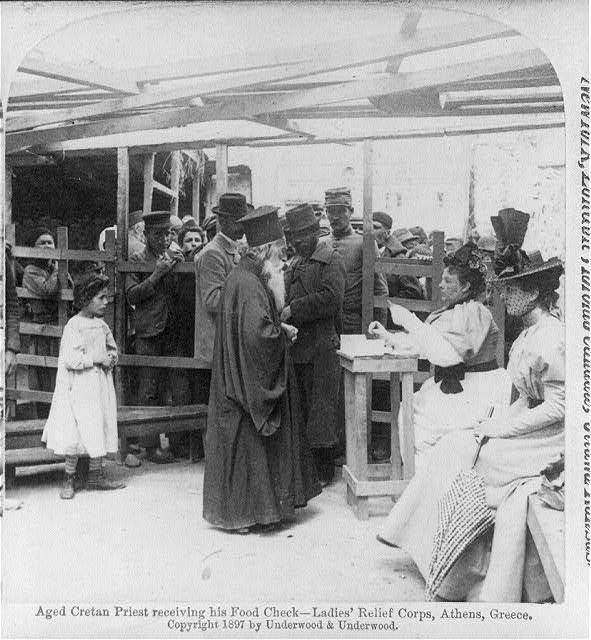 Aged Cretan priest receiving his food check [from] Ladies' Relief Corps, Athens, Greece 1897