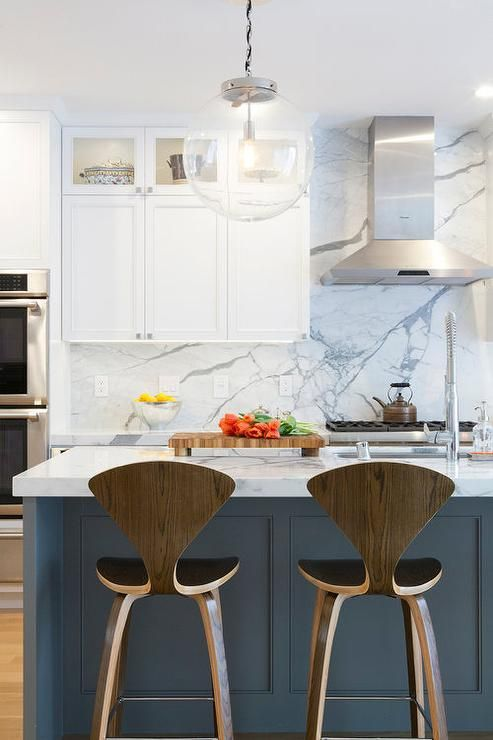 A gray and white marble slab makes up this contemporary kitchen's backsplash featuring a naturally diffused veined effect.