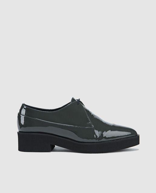 Zapatos de cordones planos elaborados en charol y con cierre de cordones altono. Tienen tacones de bajos de 2 cm de altura y terminan en punta afilada.