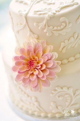 Ivory wedding cake with Victorian piping and a gorgeous floral accent.  Wedding