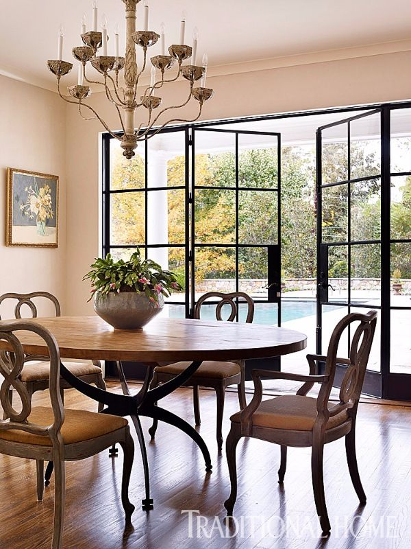 A custom iron table base mimics the metal-framed French doors and provides a contrast with the patina of the table's wood top. - Photo: Emily Jenkins Followill / Design: Chenault James