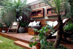 No jardim de uma casa na zona sul de São Paulo, a paisagista Gigi Botelho criou uma área de descanso sobre o deck de madeira de demolição com cadeiras de corda, bancos de madeira, treliças com trepadeira jade (Strongylodon macrobotrys) e  vasos de espirradeira (Nerium oleander), zamia (Zamia furfuracea), pacová (Philodendron martianum) e xanadu (Philodendron 'xanadu')