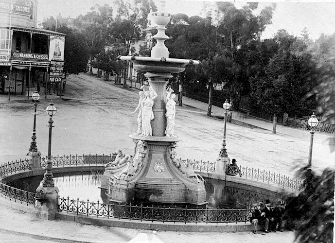The Alexandra Fountain. The shop of Manning & Company Is in the background. A number of men are seated beside the fountain. View Point, Bendigo, Victoria, Australia, 1890  W H Robinson Studio, 1890