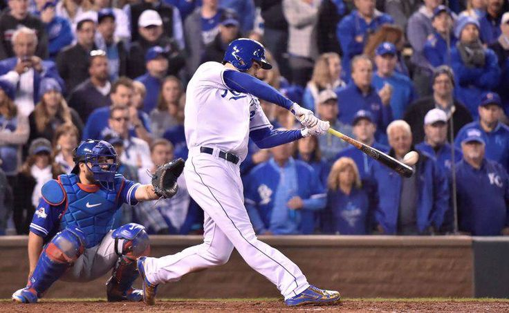 Kansas City Royals' Eric Hosmer connects on an RBI double to score Alcides Escobar as Toronto Blue Jays' catcher Dioner Navarro looks on during eighth inning game 1 American League Championship Series baseball action in Kansas City, Mo. on Friday, Oct. 16, 2015.