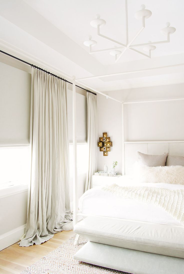 White light fixture in white bedroom with brass wall art