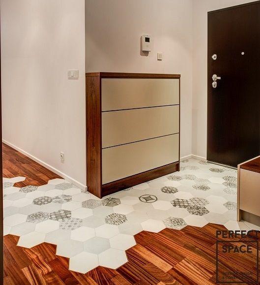 Jasny i przestronny przedpokój z ciekawą podłogą z płytek w kształcie heksagonów, które prowadzą w głąb mieszkania tworząc ścieżkę. Do tego praktyczna szafka na buty.