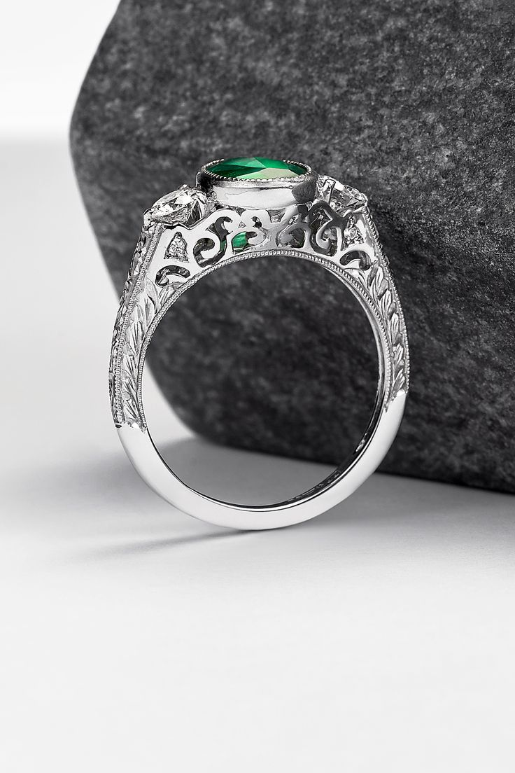 Create an engagement ring as unique as your love story! Get inspired by this vintage take on the classic trilogy - a ring by Rare Pink. Set in platinum, an oval emerald is paired with two round brilliant diamonds accented with lacy filigree. Hand engraving and milgrain delicately finish this vintage style.