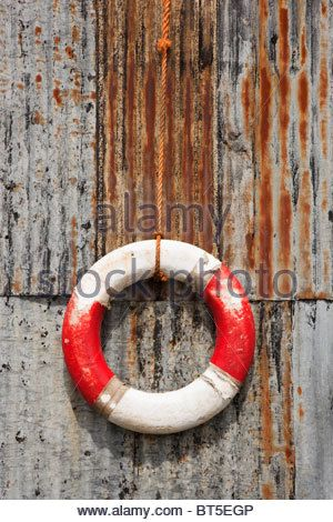 ... Britain UK Old lifebuoy ring hanging on a corrugated iron rusty metal wall - Stock Photo