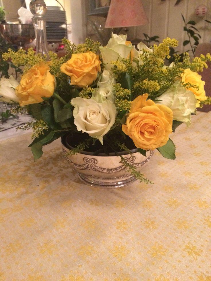 Gammel sølvbolle, lav glasskål med oasis oppi. Gule og hvite roser med små hvite blomster mellom