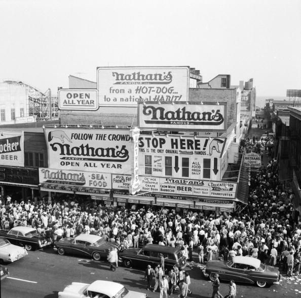 Crowds outside Nathan's famous hotdog stand on Coney Island, New York. Seafood, hot french fries, beer, chow mein, barbecue, hamburger, roast beef. Getty Images. George Heyer.