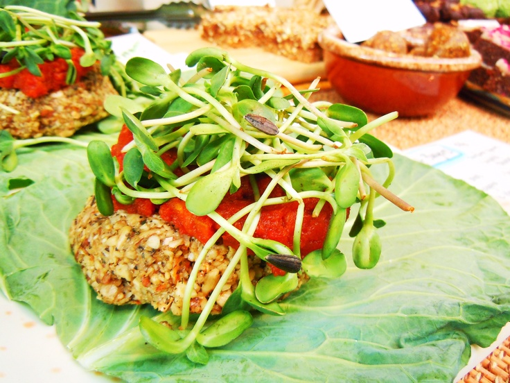 """Another personal fave, their raw vegan burgers.  This one is the nut burger with raw almonds, sunflower seeds and more on collard green """"bun"""" with sundried tomato puree and sunflower sprouts"""