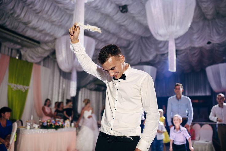 Statt Brautstrauß werfen, englische Tradition für die Single-Männer: Bräutigam wirft Strumpfband auf Hochzeitsfeier