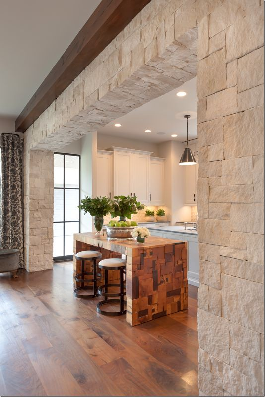 Archway of rough limestone divides the kitchen and the family room. Photo: Connie Anderson
