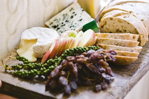 Create a gourmet cheese platter with beautiful assorted cheeses and home-made walnut bread.