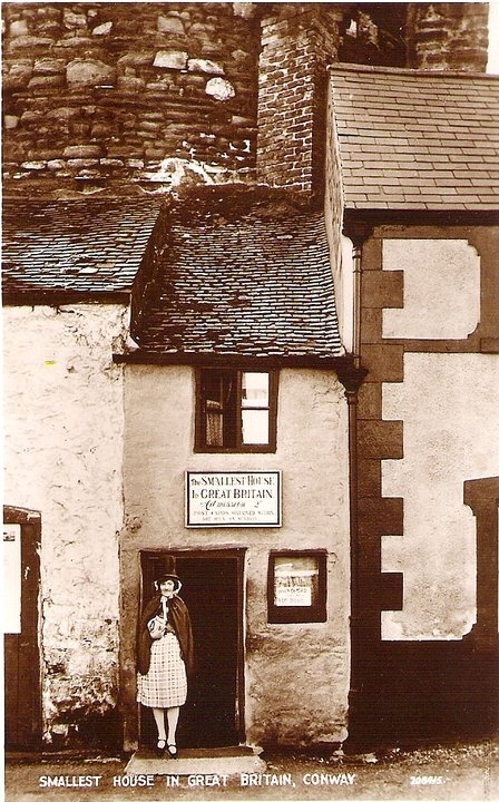 "''Smallest House in Great Britain"" postcard, (c.1920s/30s). The Quay House, is a tourist attraction on the quay in Conwy, Wales with a floor area of 10 feet by 6 feet & a height of 10 feet 2 inches. It was used as a residence from the 16th century until 1900; as its name indicates, it is reputed to be Britain's smallest house. The house was lived in until 1900, when the owner was a 6 ft 3 fisherman & the rooms were too small for him to stand up in fully & he eventually was forced to move."