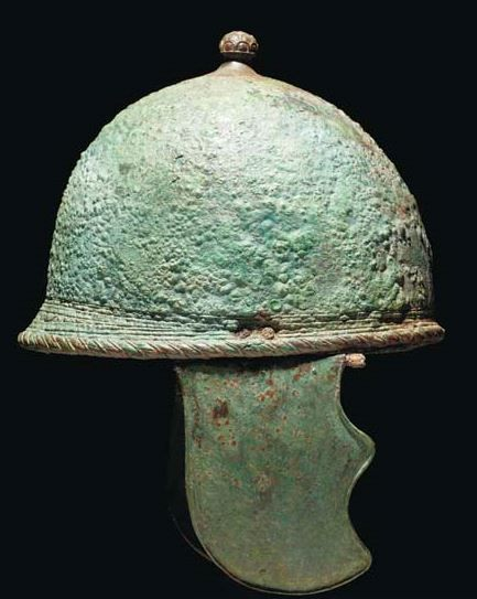 Montefortino helmet, circa 350-250 B.C. The crown topped by rosette finial, the narrow rear peak with hatched 'rope' border extending around the helmet perimeter, twin attachment rings on the underside, with cusped cheekpieces, 33 cm high. Private collection, from Christie's auction