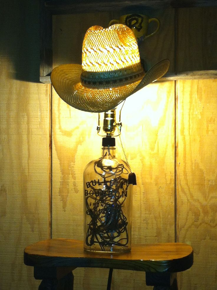 This lamp was made from large whiskey bottle, old barbed wire shoved inside and  an old cowboy hat.