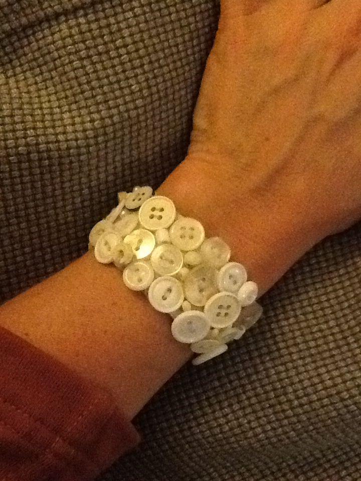 Armband gemaakt van breed elastiek waar kleine knoopjes op vast genaaid zijn. Ook leuk met gekleurde knopen!