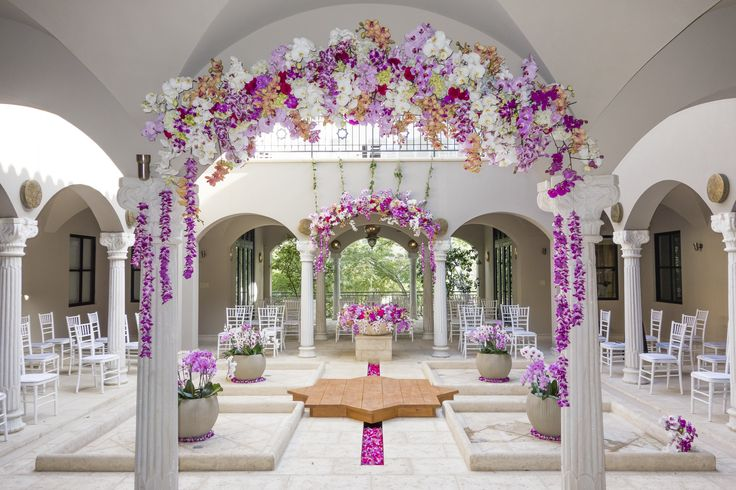Wedding ceremony entrance. Flower decoration with bright purple - pink - white orchids