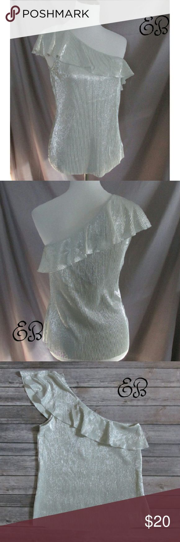 """""""Friday Night Lights"""" Tank Gorgeous silver tank in a one shoulder style. Has ruffle details at the neck. The tank itself has tiny accordion pleating. This top is not lined but it is soft to the touch. The pleats make the metallic silver spark and give movement.  This top will pick up the light so nicely at night or in low lighting.  100% Polyester   DD 11.1.17 Eclectic Betty Tops Tank Tops"""