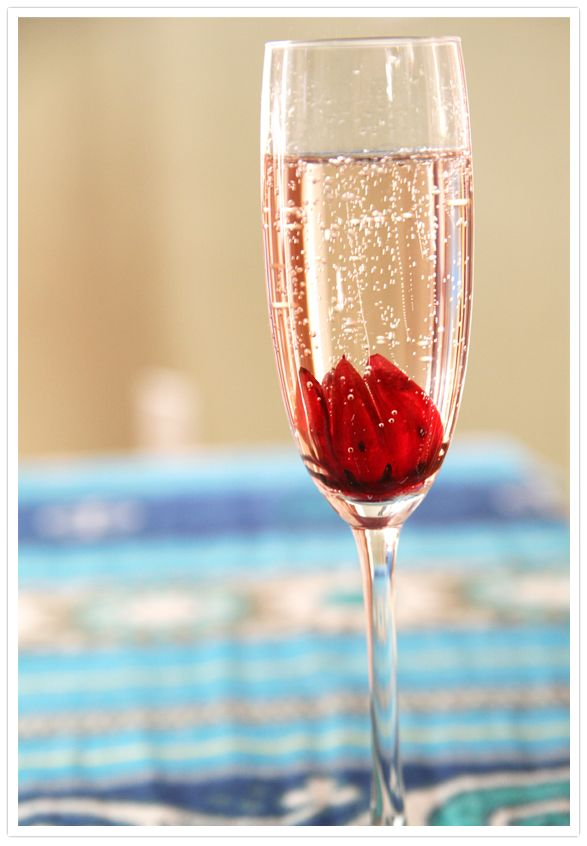 A really easy and fairly inexpensive way to impress you guess. This champagne glass has Hibiscus flowers in. You can buy them in a jar closed and when you put them in champagne they open and look beautiful. Also many are in flavoured syrups which flavours the champagne and often colours it a beautiful pink!