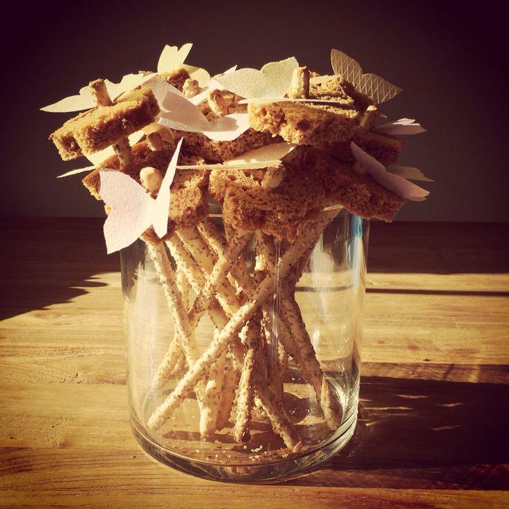 Bloemen van ontbijtkoek op soepstengels met vlinders van eetpapier.