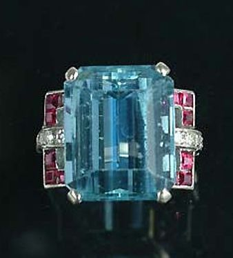 An art deco aquamarine dress ring, circa 1930,  the rectangular step-cut aquamarine, to stirrup-shaped calibré-cut ruby and single-cut diamond shoulders