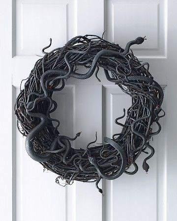 This is cute. Black wreath or spray paint a plain brown one. Rubber kids snake toys wrapped around the wreath can tack them with hot glue to make them stay better. I would add a sign across that says happy halloween or boo. And probably something orange