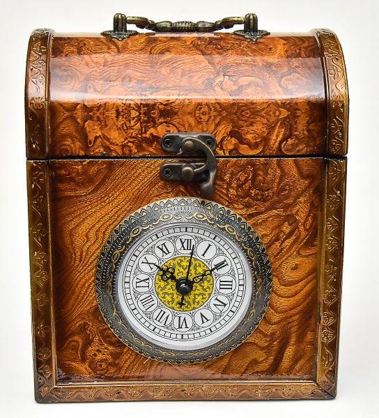 Diferente porta joias de coleção no estilo inglês confeccionado em madeira industrializada no padrão rádica com relógio à quartz na galeria central, mostrador em algarismos romanos. Acabamentos em metal. Med.: 23x16x12 cm.