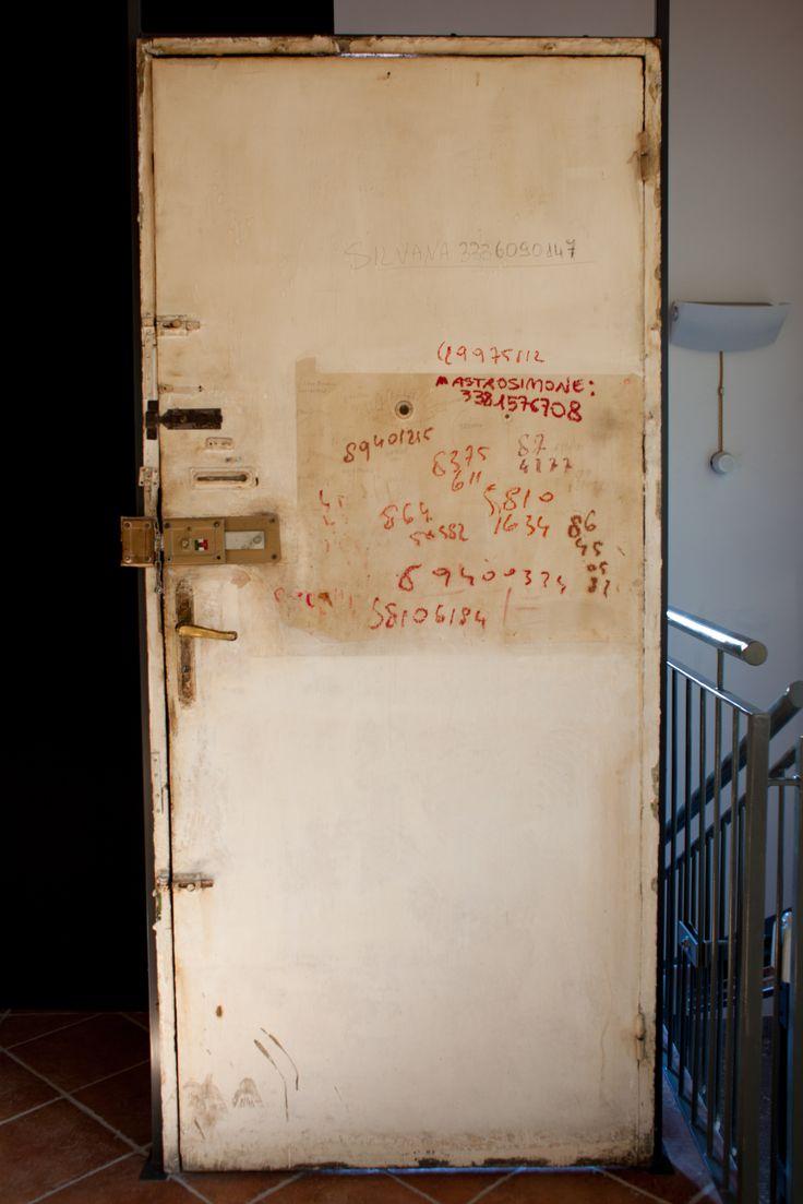 """La porta d'ingresso originale della casa di Ripa Ticinese della poetessa Alda Merini, dove sono ben visibili le """"scritte a rossetto"""" dei numeri di telefono di alcuni amici."""