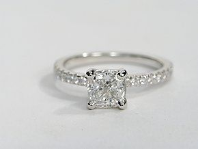 This is basically what I want. White gold, thin band with diamonds, and a princess cut diamond in the middle