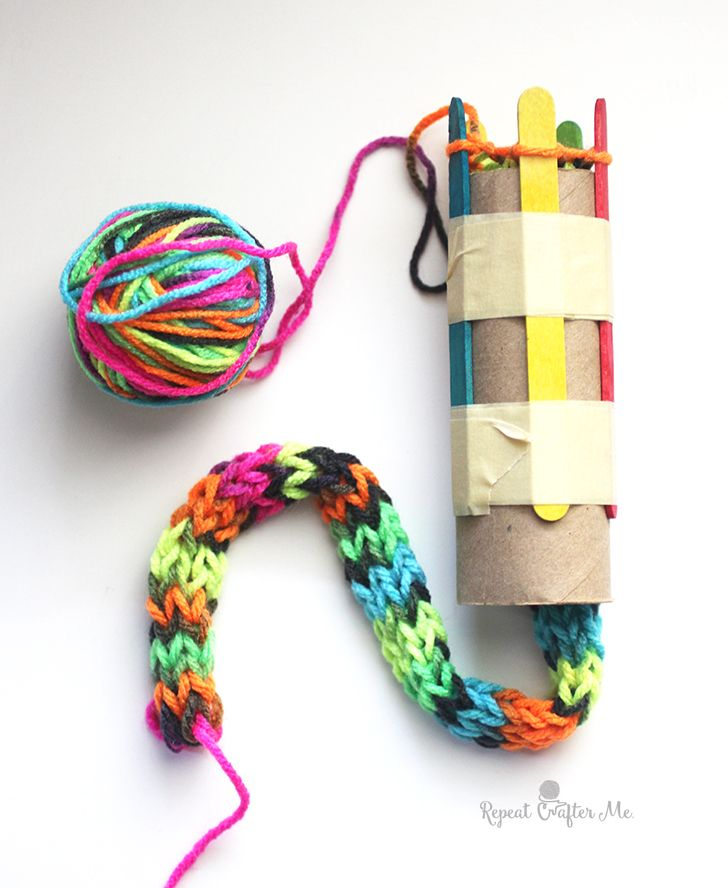"I've been busy working on setting up a project for my sons 1st grade class! It's an easy ""knitting"" project that is perfect for elementary age kids. With a cardboard roll, tape, and popsicle sticks, you can set up a simple loom. Then just like you would finger weave, you wrap the yarn around the tops …"
