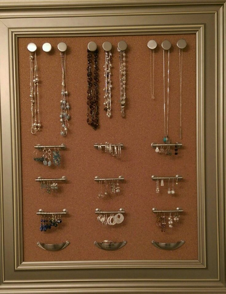 Homemade jewerly organizer made from a beautifully framed corkboard. Add drawer pulls, and knobs and you have something that's both beautiful to look at and practical at once. Hang this in the bathroom or wherever you get dressed and you have all your jewerly visible to choose from!