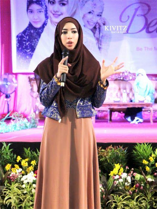 dark brown hijab, blue metallic jacket with flawless brown long dress
