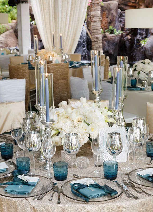 Blue taper candles placed in tall silver candlesticks add tons of drama and opulence to this white and silver tablescape.