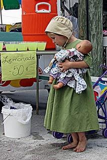 """""""Child and doll at the market""""  Dit meisje draagt niet een stoffen Amisch doll, maar een doll van """"deze"""" tijd. Ik ben zo benieuwd naar de veranderingen binnen de tradities. Wat een plaatje."""
