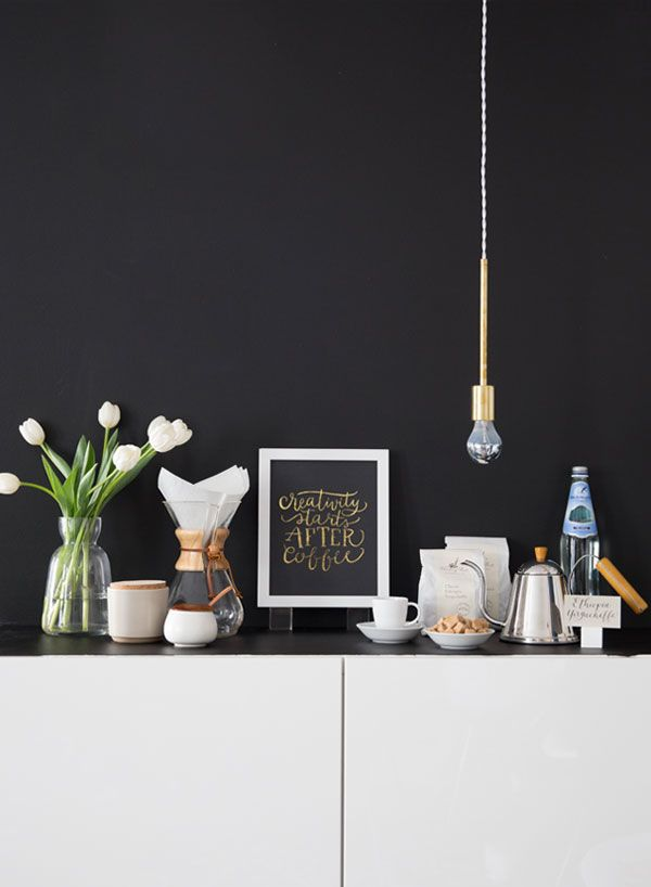The Metal ware is accentuated against the black backdrop wall.