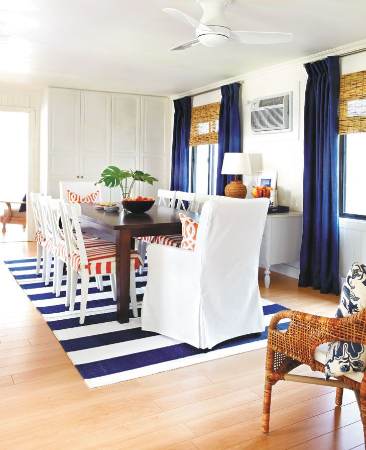 Easy striped slipcovers and a striped flat-weave rug give this room a relaxed #nautical feel. The quiet star of the room is a white paneled cabinet that provides an abundance of storage. #diningroom