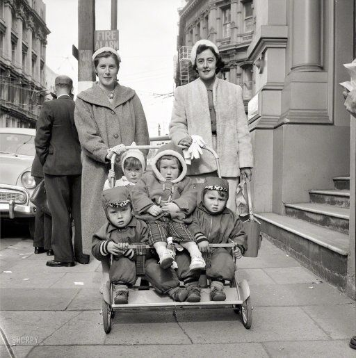 """Aug. 21, 1959, somewhere in New Zealand. """"Two women with four small children in a pushchair on a city street, probably Wellington."""" Evening Post newspaper photograph collection, Alexander Turnbull Library."""