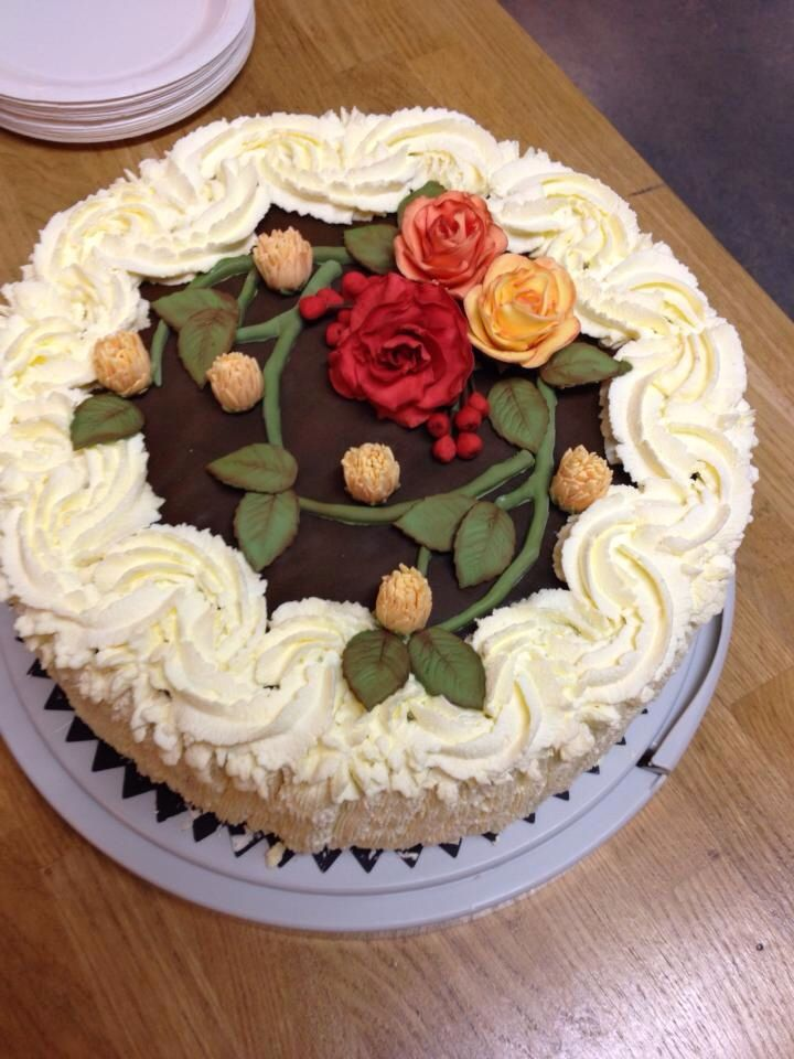 Whipped cream cake with fondant roses in autumn colors.