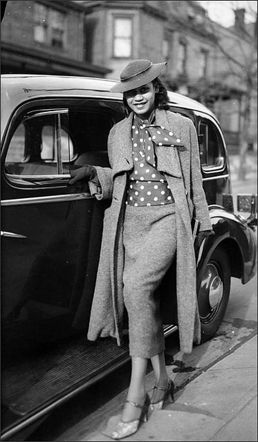 An African American woman posed next to car on Mulford Street, Homewood (Pittsburgh, PA), c. 1937