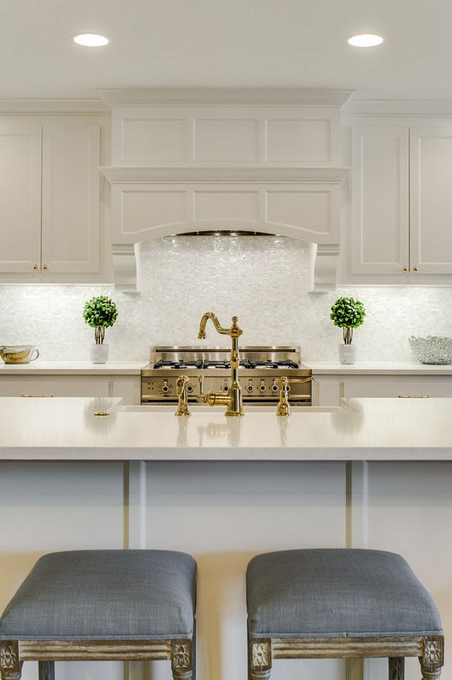 White kitchen with brass faucet and grey linen counterstool. White kitchen with…