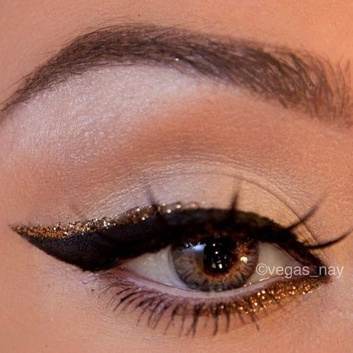 thick black cat eye/winged eye liner with a touch of gold sparkle eye liner on top and bottom. do not like the mascara on the top lashes though.... New Years make up !!!