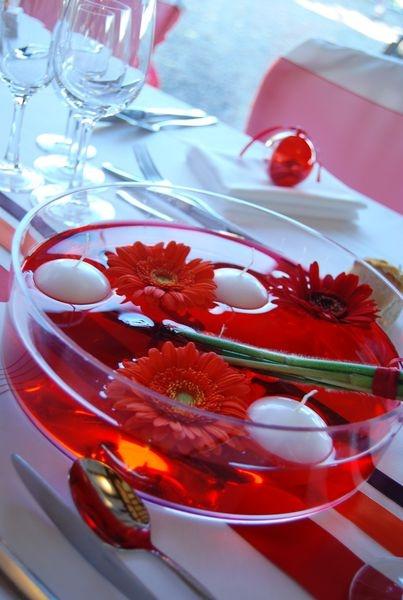 Hochzeitsdeko mit roten Gerberas und schwimmenden Kerzen.