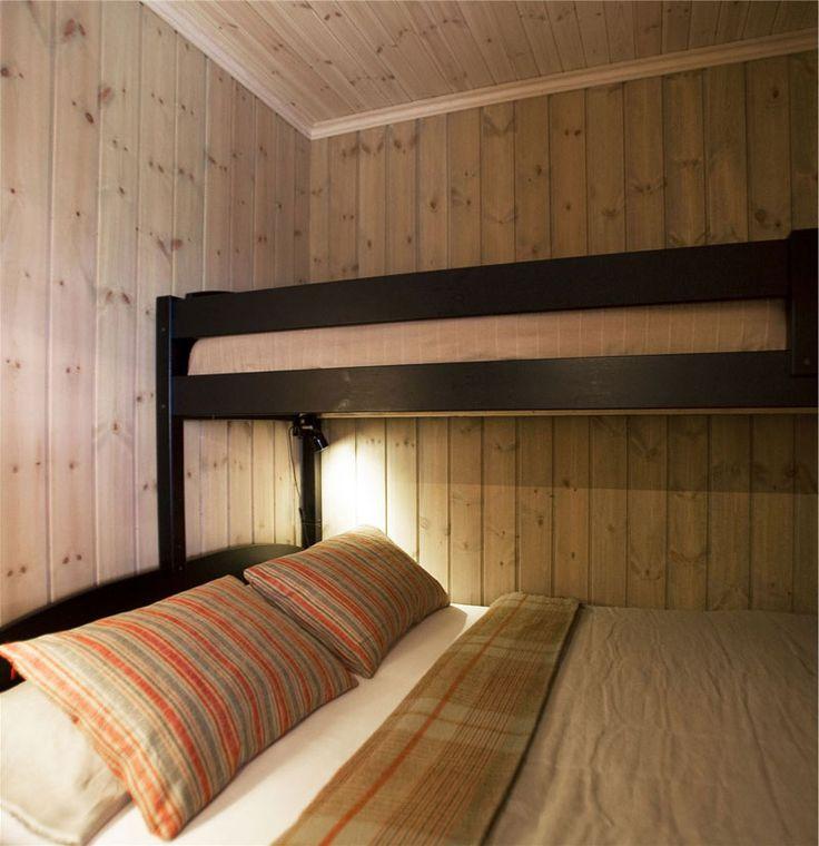 Soverom med en lysere interiørbeis. Tekstilene er i rød- og bruntoner.