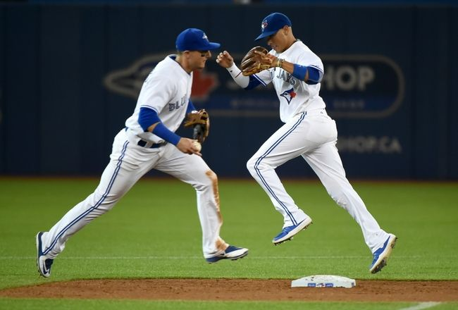 Sep 2, 2015; Blue Jays shortstop Troy Tulowitzki and second baseman Ryan Goins converge at second base during a force out against Cleveland Indians in the ninth inning at Rogers Centre. MLB. Baseball.